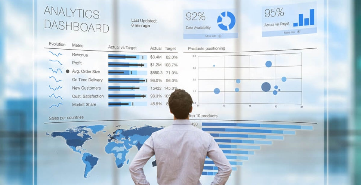Man with hands on hips looking at at a large projection of a business analytics dashboard